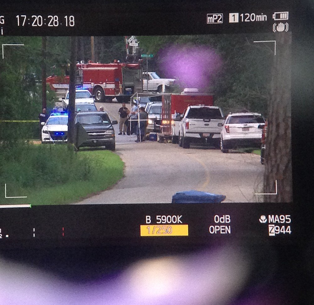 A FOX10 News camera monitor shows the scene outside a home in Flomaton, where two people were found dead inside. Photo: Kendall Faust, FOX10 News