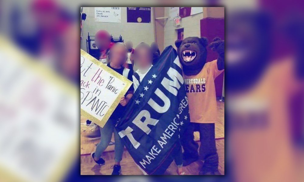 "A picture shows two girls holding signs and standing alongside the Robertsdale High School mascot. One sign is a ""Trump Make America Great Again"" banner. The other is a homemade poster that reads, ""Put the 'Panic' Back in Hispanic."" (Facebook)"
