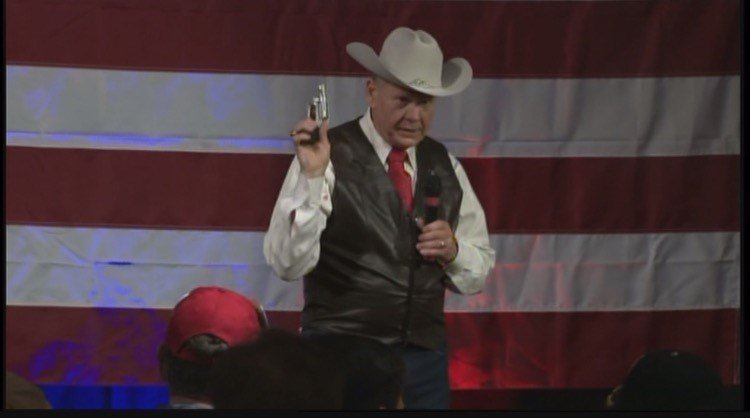 Roy Moore pulled out his gun at a rally on Monday, September 25th. Photo: FOX10 News.