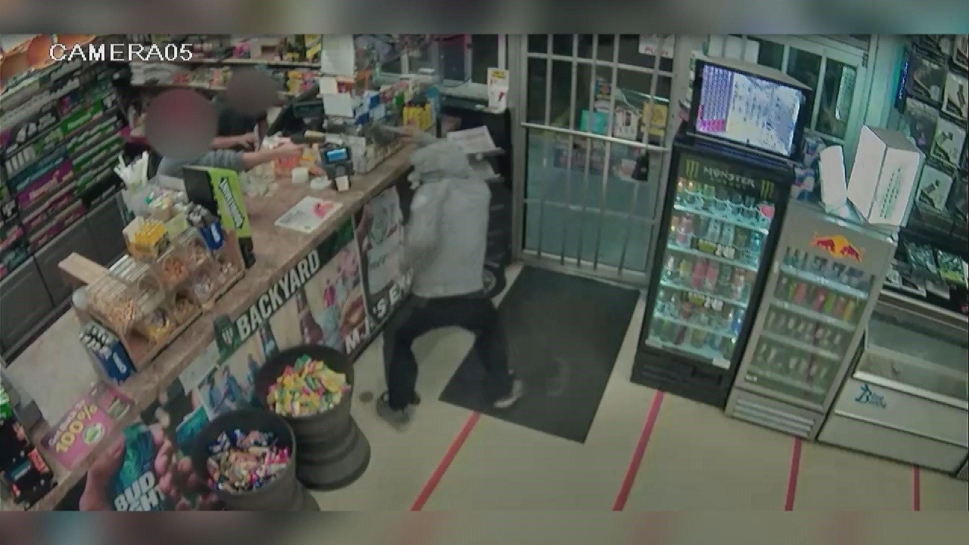Video from the Riverside Food Mart shows a clerk pointing a gun at an armed robber. Photo: Riverside Food Mart video.