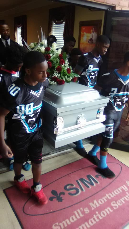 Panthers football team act as pall bearers at their coach's funeral