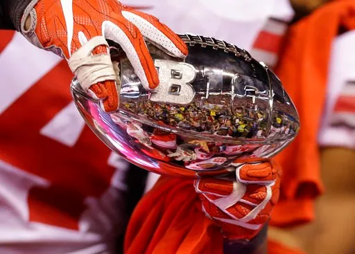(AP Photo/AJ Mast). Ohio State players hold the championship trophy following the Big Ten championship NCAA college football game against Wisconsin, early Sunday, Dec. 3, 2017, in Indianapolis.