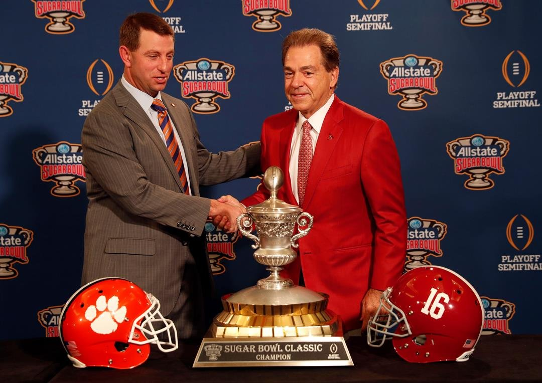 Clemson head coach Dabo Swinney and Alabama head coach Nick Saban, left, pose with the Sugar Bowl trophy for their upcoming semi-final playoff game, for the national championship, in New Orleans, Sunday, Dec. 31, 2017. (AP Photo/Gerald Herbert)
