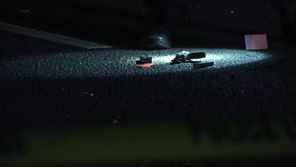 Police shine light on a gun lying in the parking lot of an Airport Boulevard shopping center after a shooting took place Saturday night, Jan. 13, 2018.