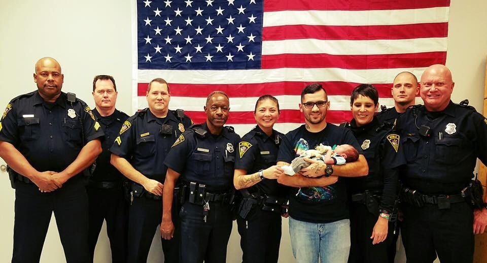 Officer Justin Billa took a picture with his third precinct co-workers last year with his son in his arms. Photo: MPD.