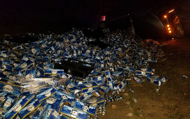 Truck carrying about 60000 pounds of Busch beer overturns