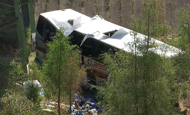 A charter tour bus that was transporting Texas band students home from a trip to Disney World lies where it crashed off I-10 in Alabama. (FOX10 News)