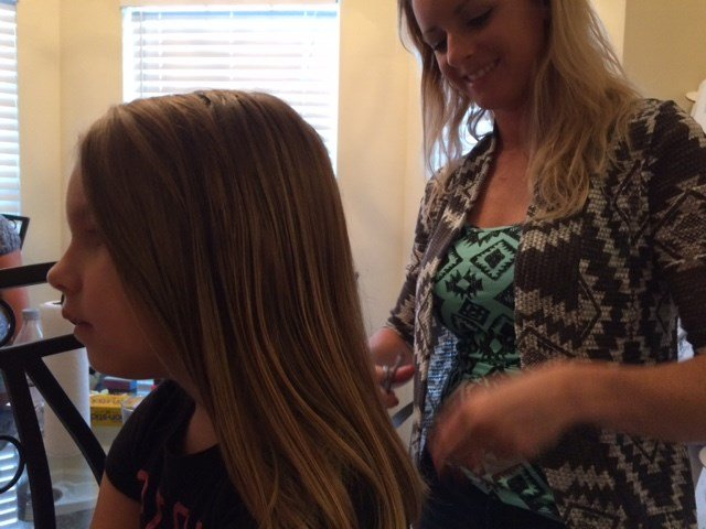 Milstead cuts another girl's hair in her home.